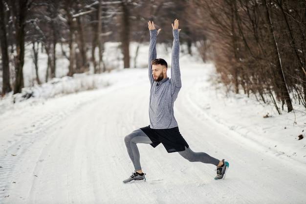 冬の雪の上で自然の中でウォームアップエクササイズをしているスポーツマンに合いましょう。