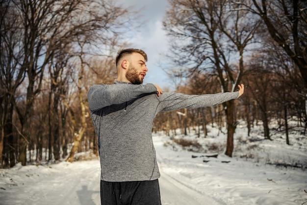 눈 덮인 겨울 날 자연 속에 서 있는 동안 워밍업 운동을 하는 스포츠맨. 겨울 피트니스, 건강한 라이프 스타일