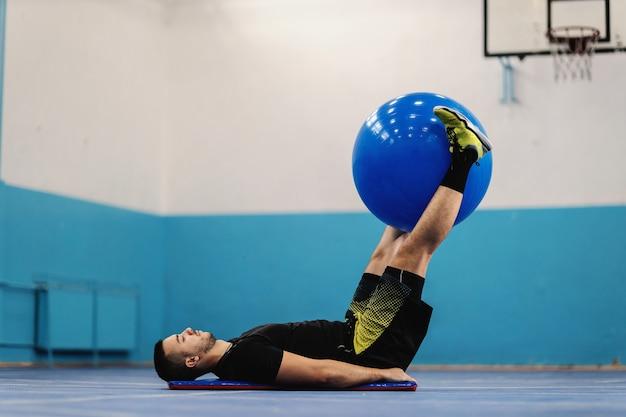 스포츠 홀에서 필라테스 공을 사용하여 크런치를 수행하는 우수한 모양의 스포츠맨을 맞 춥니 다.