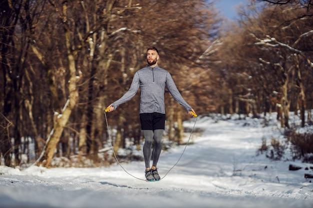 雪の降る冬の日に森で縄跳びをするスポーツマンにぴったり。健康的な生活、冬のフィットネス、スポーツウェア