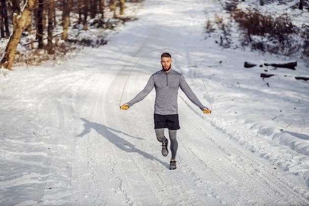 눈 덮인 겨울 날에 자연의 흔적에 밧줄을 점프하는 스포츠맨을 맞추십시오.