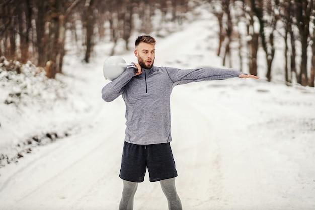 森の中の雪道に立っている間、ケトルベルを持ち上げるスポーツマンに合います。冬のフィットネス、健康的な生活、ボディービル