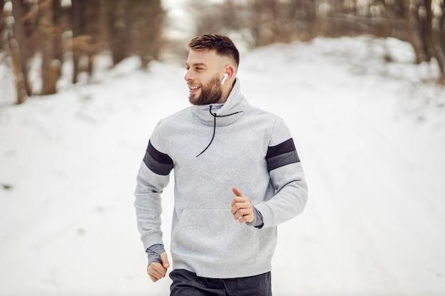 冬の雪の上で自然の中で走っているスポーツマンに合いましょう。健康的なライフスタイル、冬のフィットネス、寒さ
