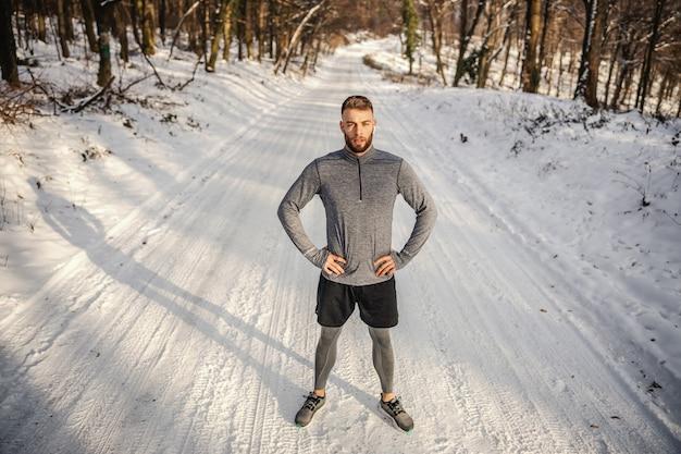 Подходит спортсмен, стоя на природе с руками на бедрах в снежный зимний день.