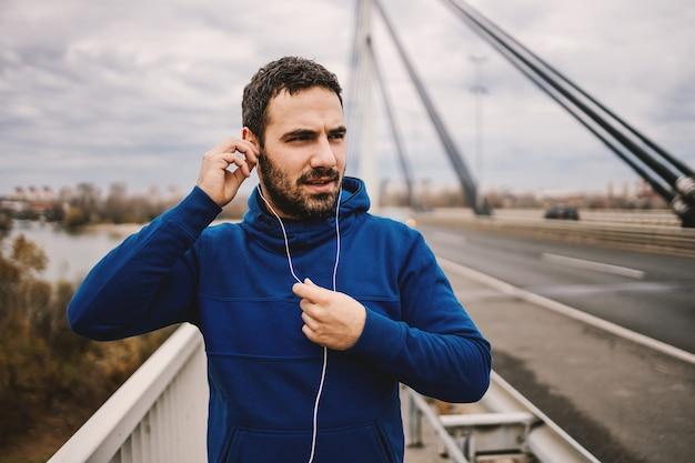 Подходит спортсмен, стоящий на мосту и надевающий наушники.