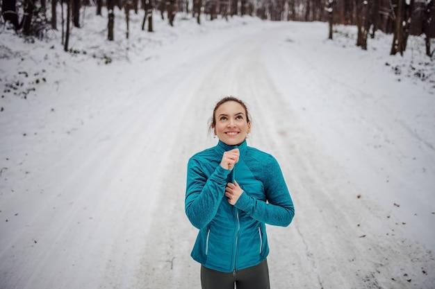 自然の中の雪道に立っている間、スポーツウーマンのバックリングジャケットを着用してください。雪、冬のフィットネス、寒さ、健康的な生活、肌寒い