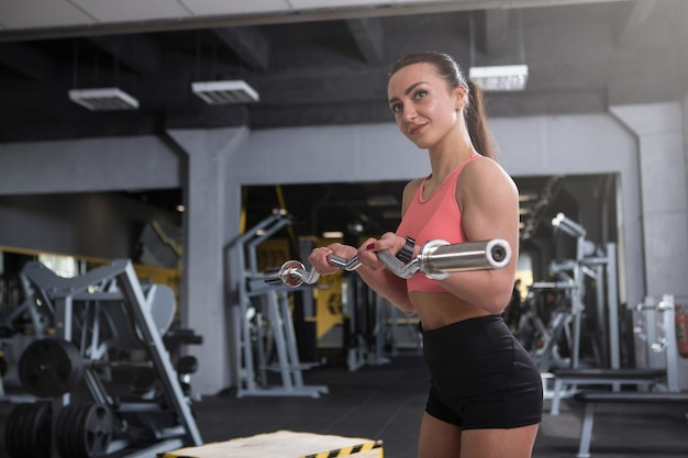 Fit sportswoman doing biceps exercise with barbell at the gym, copy space