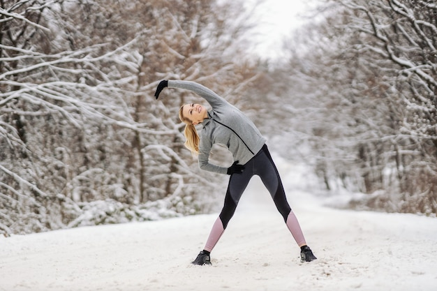 Fit sportswoman doing stretching and warm up exercises while standing at snowy path in nature at winter. winter fitness, outdoor fitness, healthy lifestyle
