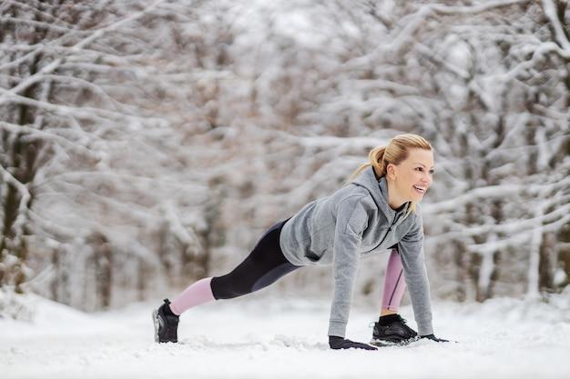 겨울에 눈 덮인 길에 있는 숲에서 워밍업과 스트레칭 운동을 하는 운동복을 입은 운동가를 맞으세요. 건강한 습관, 겨울 피트니스