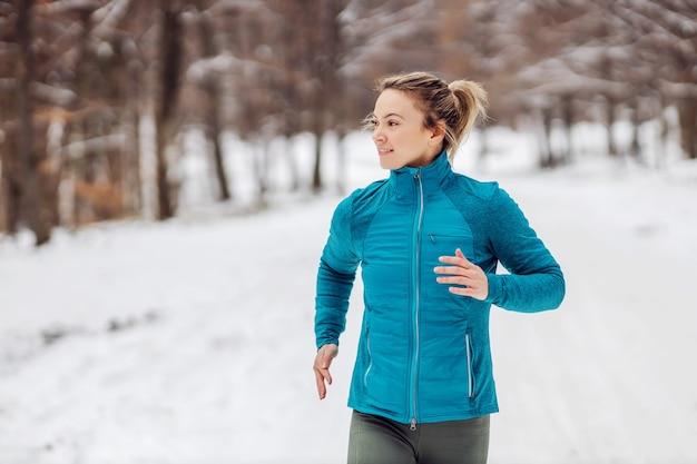 雪の降る天候で自然の中でジョギングするスポーツウーマンにぴったりです。寒さ、雪、健康的な生活、フィットネス