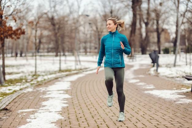 雪の降る冬の日に公園の小道をジョギングするスポーツウーマンにぴったり。レクリエーション、雪の天気、冬の日