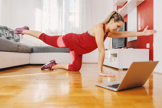 Fit sportswoman kneeling on the floor at home and doing fitness exercises while following online class.