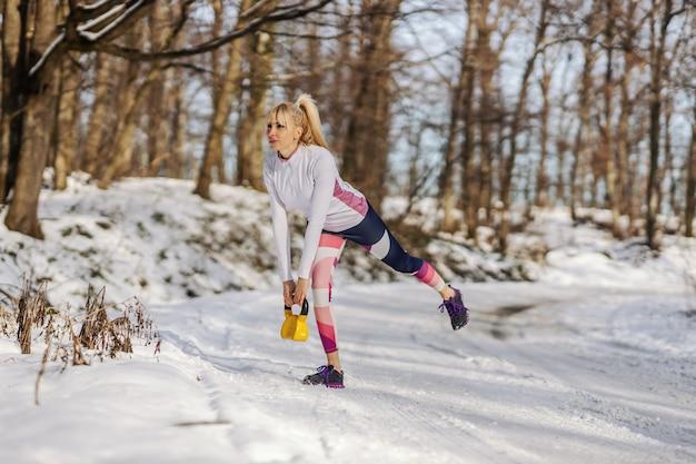 Подходит спортсменка, поднимая гирю, стоя на снежной тропе в природе зимой. тяжелая атлетика, бодибилдинг, зимний фитнес
