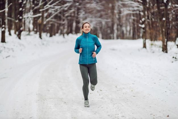 雪に覆われた肌寒い冬の日に自然の中で走っているスポーツウーマンにぴったりです。寒さ、雪、健康的な生活、フィットネス、森