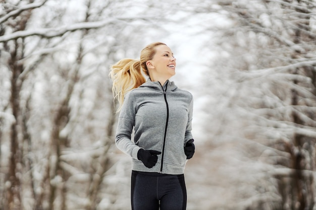 Fit sportswoman running in nature at winter snowy day. outdoor fitness, healthy lifestyle, chilly weather