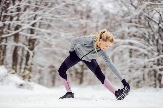 Фитнес спортсменка стоит на природе и зимой делает разминку и растяжку. снежная погода, зимний фитнес