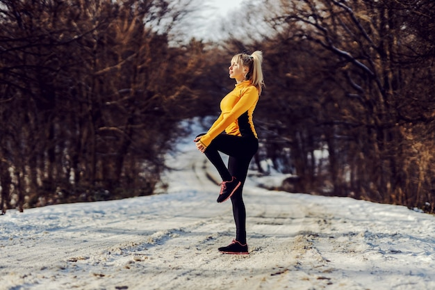 雪道で片足で立って、自然の中でストレッチやウォームアップのエクササイズをしているスポーツウーマンにフィットします。ライフバランス、健康的なライフスタイル、冬のフィットネス