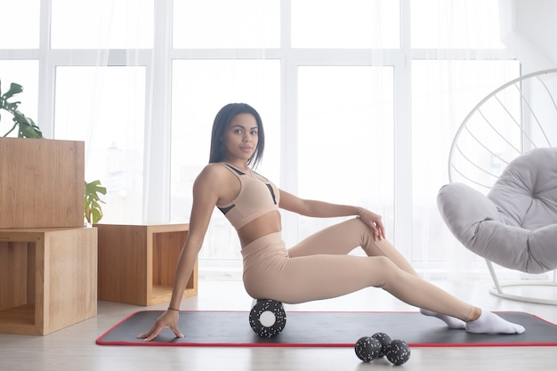 Спортивная черная женщина в спортивной одежде, ролл на пене, миофасциальный массажный ролик, массирующий мышцы на полу коврика для йоги дома