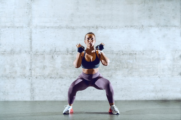 Fit sporty brunette in sportswear with ponytail doing squats while holding dumbbells