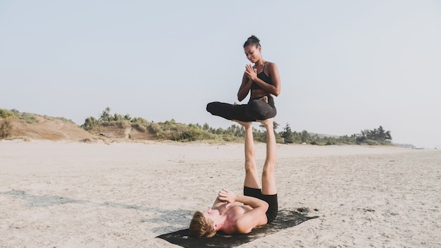 Fit спортивная пара практикующих acro йогу с партнером вместе на песчаном пляже.