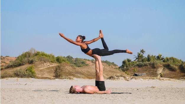 砂浜のビーチで一緒にパートナーと一緒にアクロヨガを練習するスポーティなカップルを合わせてください。