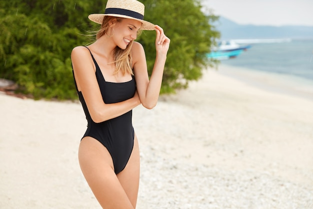 Fit sporty female stands on tropical beach, wears summer hat and swimsuit, relaxes by ocean, breathes fresh air, looks down with happy expression, being professional photo model. nature and relaxation