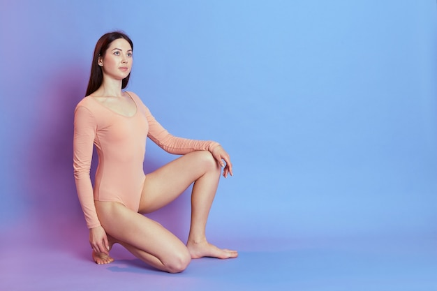 Fit and sporty girl wearing beige bodysuit sitting on one knee isolated over blue wall with pink neon light, female with perfect body. sport, fitness, diet, and healthcare.