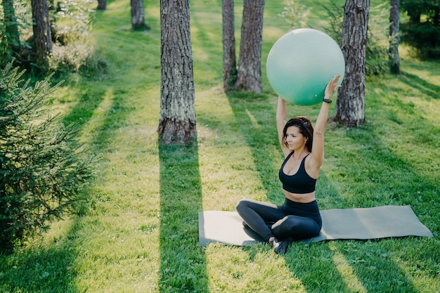 Fit sporty woman exercises with fitness ball sits on mat in lotus pose