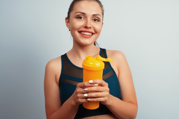 Fit sporty woman holding mineral water bottle in her hand