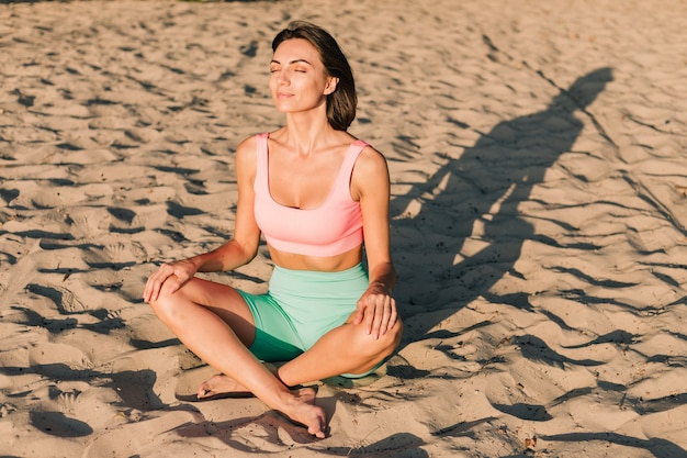 Fit sporty woman in perfect shape at sunset at beach in yoga pose calm