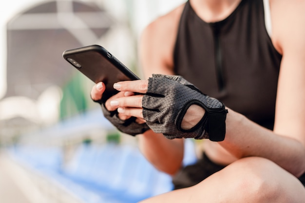 Fit sporty woman uses phone on the stadium in the morning during fitness workout