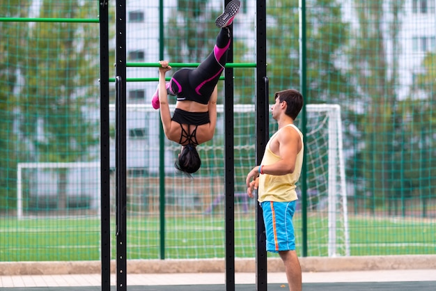 Fit sporty young woman working out on parallel bar