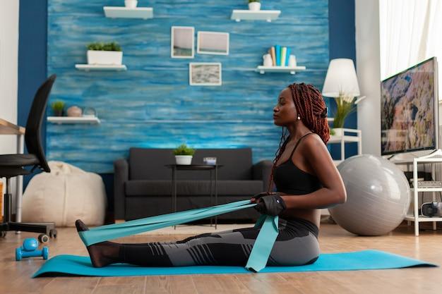 Montare una forte donna afro che si allena nel soggiorno di casa usando la fascia di resistenza, seduta sul tappetino fitness tirando per i muscoli della schiena