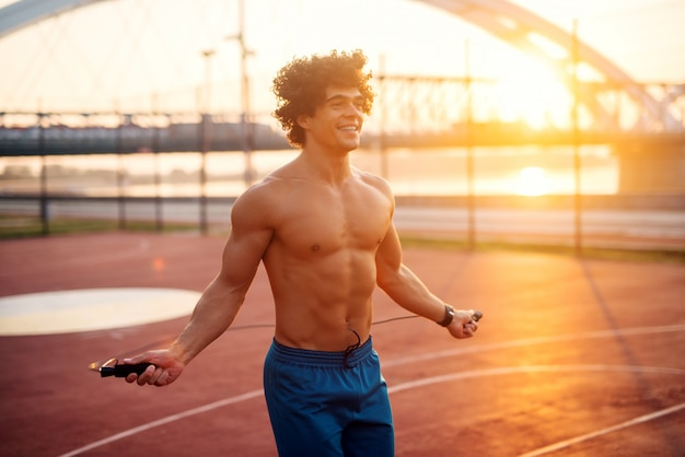 Fit strong good looking man jumping rope early in the morning outside