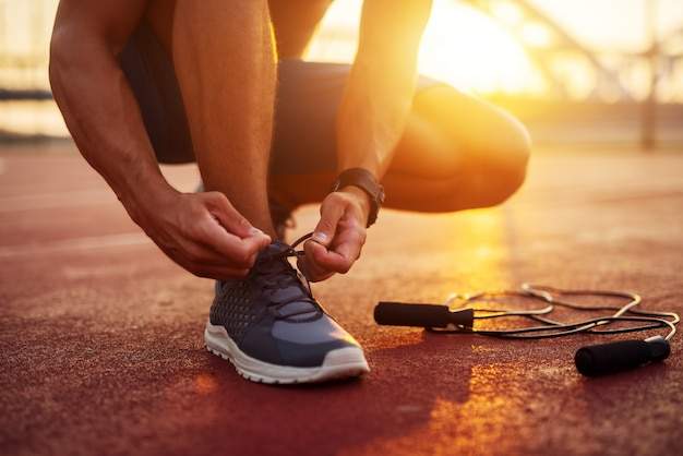 Fit сильный молодой человек завязывает шнурки и готовится к ранним солнечным утренним тренировкам на улице