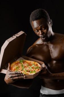 골판지 상자에 피자와 함께 놀란 흑인 남자를 맞추십시오. 고객에게 배달된 피자와 함께 옷을 벗은 잘생긴 아프리카 남자.