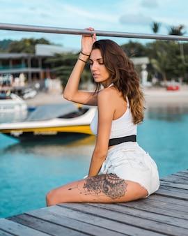 Подтянутая загорелая татуированная брюнетка в голубых джинсовых шортах и белом облегающем топе сидит на деревянном пирсе в свете заката