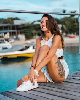 Fit tanned brunette tattooed woman in light blue jean shorts and white fitting top sits on wooden pier at sunset light