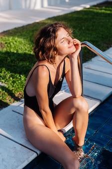 수영장에있는 빌라 호텔에서 검은 색 피팅 수영복에 검게 그을린 갈색 머리 여자를 맞추십시오.