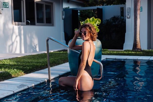スイミングプールのヴィラホテルで黒のフィッティング水着に日焼けしたブルネットの女性をフィットさせる