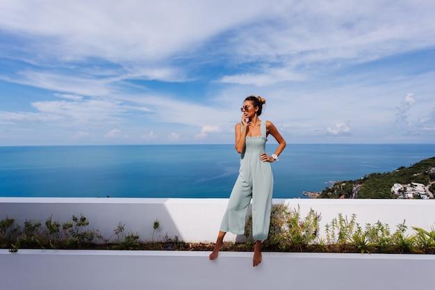 놀라운 열대 바다를 볼 수있는 고급 빌라의 teracce 발코니에 전체적으로 밝은 파란색 민트 색상의 검게 그을린 백인 여성