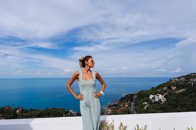 Fit tanned caucasian woman in light blue mint color overall on teracce balcony of luxury villa with amazing tropical sea view