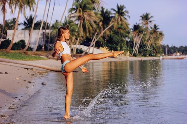 열 대 해변에서 일몰에 흰색 상단과 파란색 팬티에 무두 질된 슬림 백인 여자를 맞습니다. 태양과 바다를 즐기는 좋은 모양의 무두질 된 여성