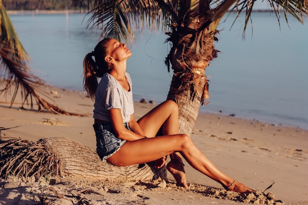 Fit tanned slim woman in top and shorts on tropical beach at sunset