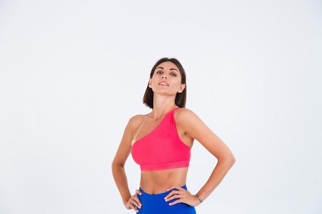 Подтянутая загорелая спортивная женщина с прессом, фигурами фитнеса, в топе и синих леггинсах на белом