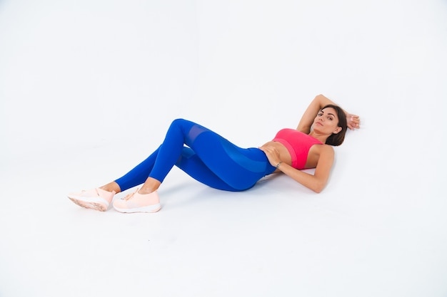 Fit tanned sporty woman with abs, fitness curves, wearing top and blue leggings on white