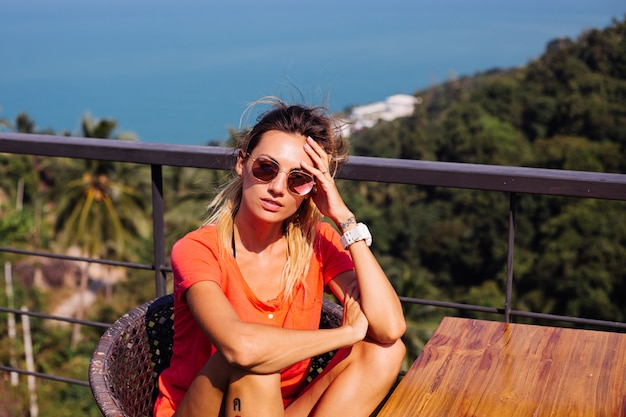 Fit tanned tattooed caucasian european woman with sport body and abs, in jean shorts and red orange shirt