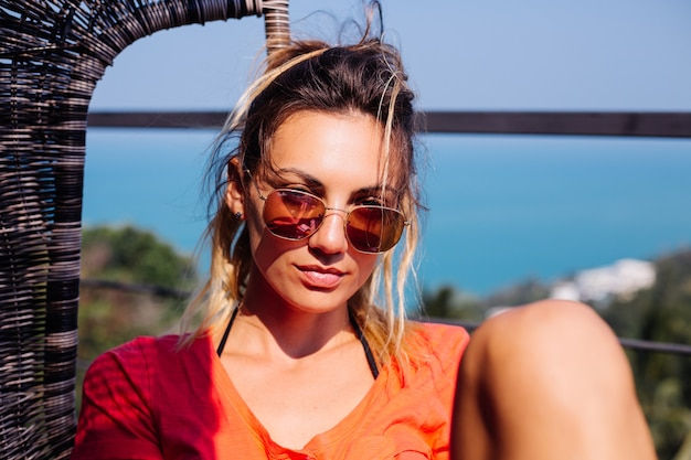 ジーンズのショートパンツと赤オレンジ色のシャツで、スポーツボディと腹筋を持つ日焼けした入れ墨の白人ヨーロッパの女性にフィットします