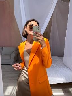 집에서 낭만적 인 베이지 색 실크 드레스와 주황색 블레이저에 무두질 된 여성이 거울에 전화로 사진 셀카를 찍습니다.