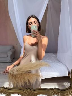 집에서 로맨틱 한 베이지 실크 드레스에 무두질 된 여자가 거울에 전화로 사진 셀카를 찍습니다.